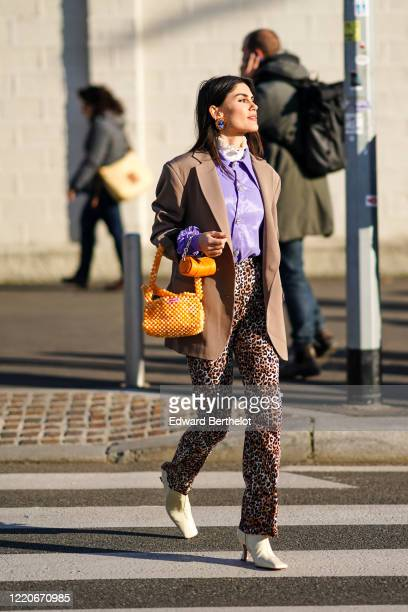 Asena Saribatur wears earrings, a purple shirt, an oversized blazer jacket, an orange beaded bag, leopard print pants, point shoes, outside Prada,...
