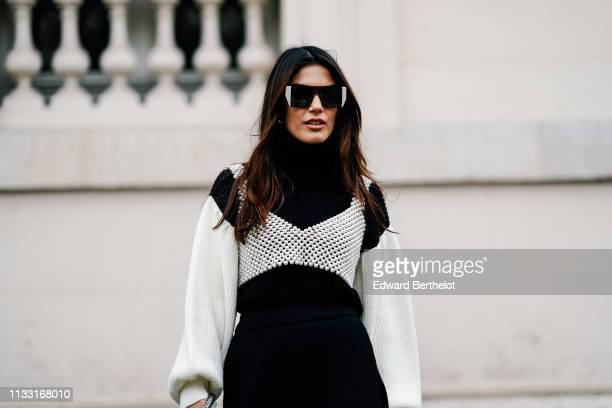 Asena Saribatur wears sunglasses, a black dress with white puff sleeves, a pearl beaded crop top, outside Issey Miyake, during Paris Fashion Week...