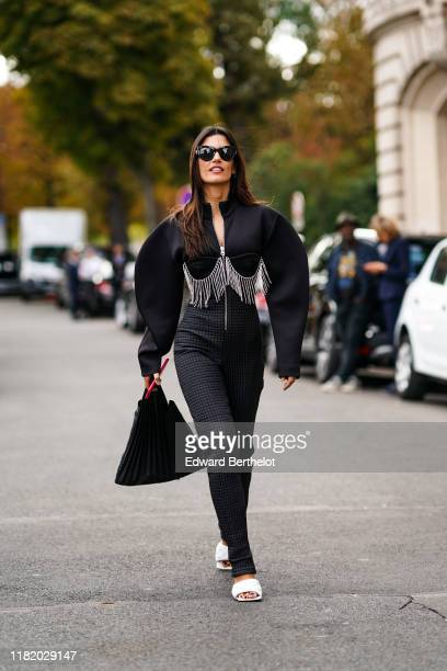 Asena Saribatur wears sunglasses a black jumpsuit with rhinestone fringes a pleated black bag white quilted mules outside Elie Saab during Paris...