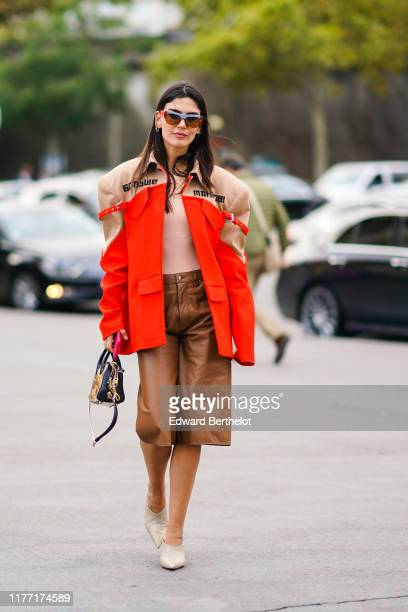 Asena Saribatur wears sunglasses earrings a sandcolor and tangerine jacket a black embroidered bag tancolor leather short pants beige pointy mules...