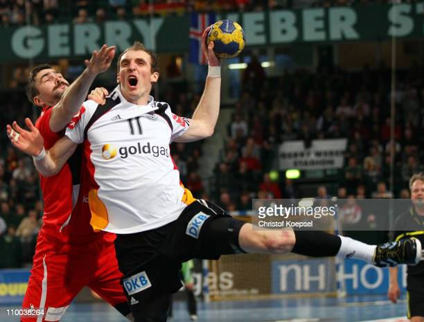 Asgeir Oern Hallgrimsson of Iceland blocks Holger Glandorf of Germany during the Handball Euro Qualifier match between Germany and Iceland at Gerry...