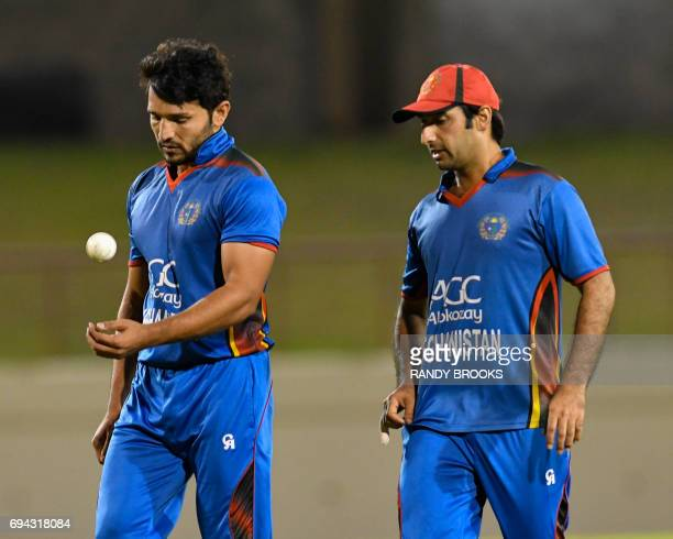 Asghar Stanikzai of Afghanistan speaks with teammate Gulbadin Naib during the 1st ODI match between West Indies and Afghanistan at Darren Sammy...