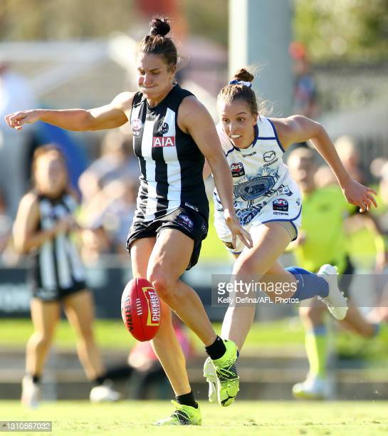 Ash Brazill of the Magpies kicks the ball under defensive pressure from Emma King of the Kangaroos during the AFLW Finals Series match between the...