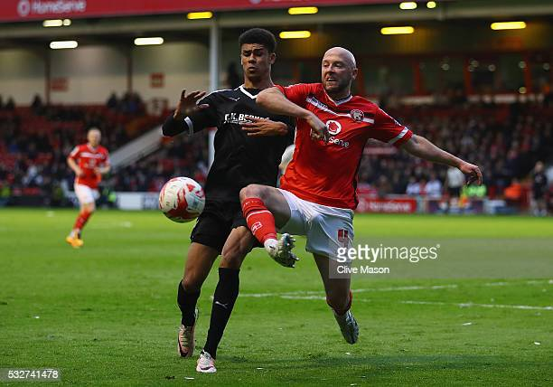 Ash Fletcher of Barnsley is tackled by James O'Connor of Walsall during the Sky Bet League One play off second leg match between Walsall and Barnsley...