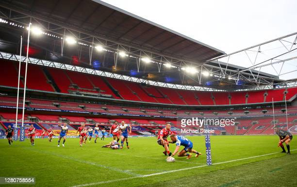 Ash Handley of Leeds Rhinos scores his sides second try as he is put under pressure by Tui Lolohea of Salford Red Devils during the Coral Challenge...
