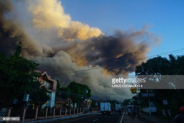 Ash rises up from the Mayon volcano as it continues to erupt seen from the town of Daraga in Albay province south of Manila on January 24 2018...