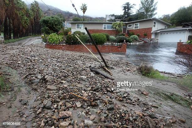 Ash rocks and mud cover a residential street below the Colby Fire burn area as a storm brings rain in the midst of record drought on February 28 2014...