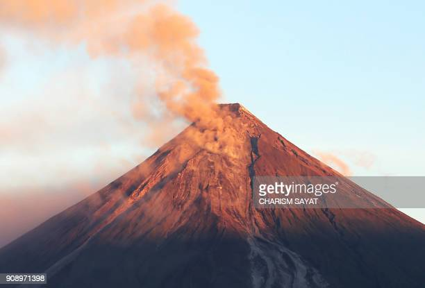 Ash spews from the Mayon volcano as it continues to erupt seen at sunrise from Legazpi City in Albay province south of Manila on January 23 2018 A...