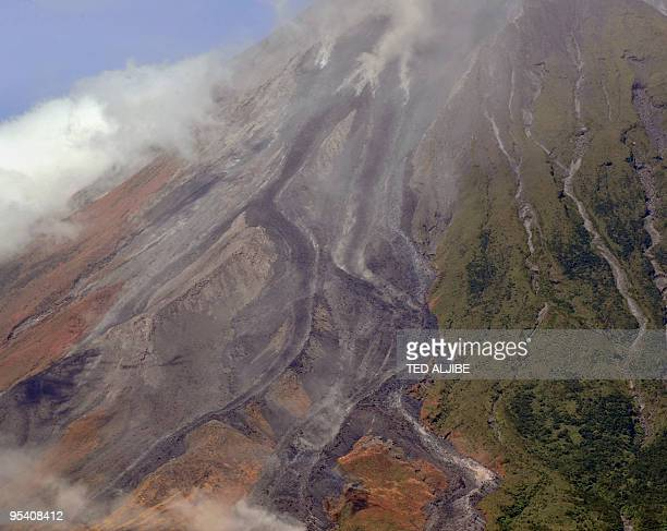 Ash spews out of the Mayon volcano's gully pictured from the city of Legazpi in Albay province 330 kms southeast of Manila on December 27 2009 The...
