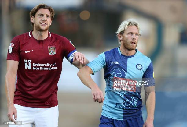Ash Taylor of Northampton Town and Craig MackailSmith of Wycombe Wanderers look on during the Carabao Cup First Round match between Wycombe Wanderers...