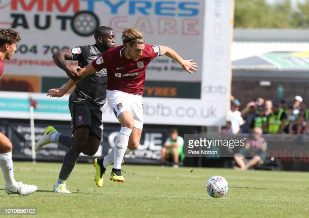 Ash Taylor of Northampton Town attempts to move away from John Akinde of Lincoln City during the Sky Bet League Two match between Northampton Town...