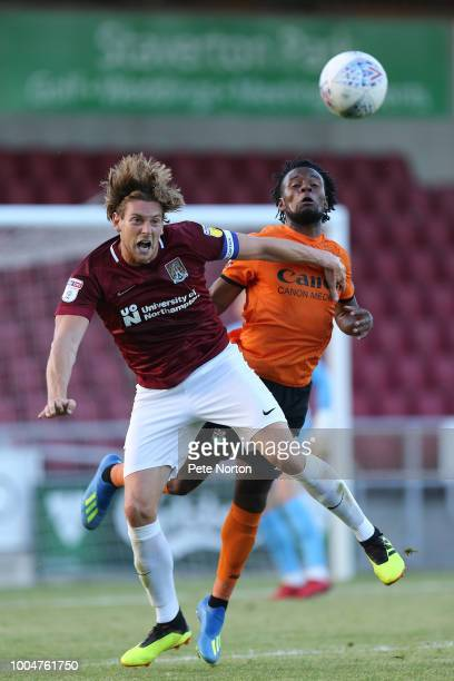 Ash Taylor of Northampton Town contests the ball with Shaq Coulthirst of Barnet during the PreSeason Friendly Match between Northampton Town and...