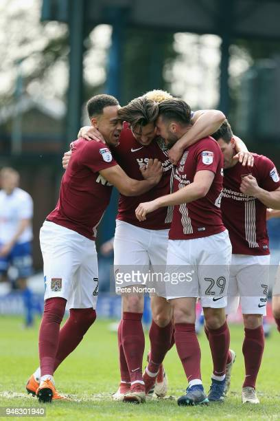 Ash Taylor of Northampton Town is congratulated by team mates after scoring his sides first goal during the Sky Bet League One match between Bury and...