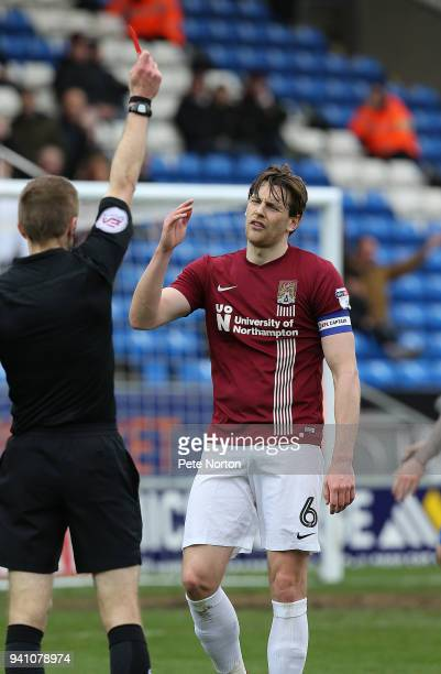 Ash Taylor of Northampton Town is shown a red card by referee Michael Salisbury during the Sky Bet League One match between Peterborough United and...