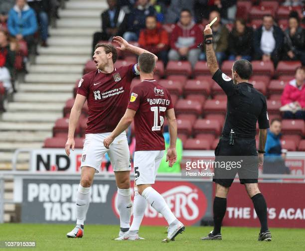 Ash Taylor of Northampton Town reacts after being shown a yellow card by referee Paul Marsden during the Sky Bet League Two match between Northampton...