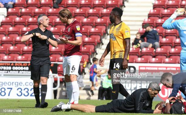 Ash Taylor of Northampton Town remonstrates with referee Seb Stockbridge as Jabo Ibehre of Cambridge United is shown a yellow card for a clash with...