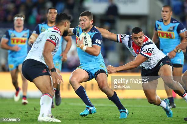 Ash Taylor of the Titans is tackled during the round 18 NRL match between the Gold Coast Titans and the Sydney Roosters at Cbus Super Stadium on July...