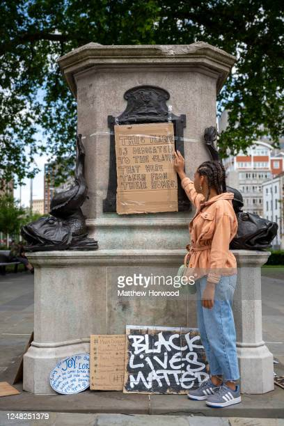 "Asha poses for a photograph at the Edward Colston statue plinth where she a taped on a cardboard sign which says ""this plaque is dedicated to the..."