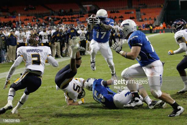 Asher Clark of the Air Force Falcons dives over Diauntae Morrow of the Toledo Rockets for a touchdown during the first half of the Military Bowl at...