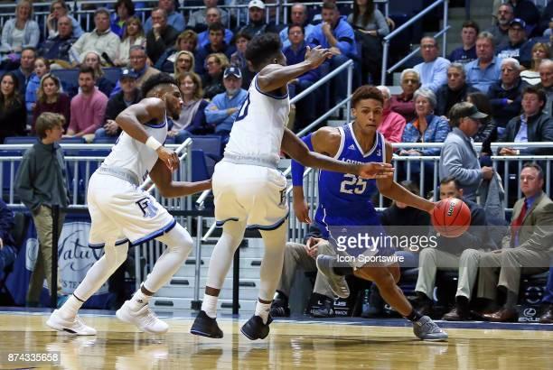 Asheville Bulldogs guard MaCio Teague doubledteamed by Rhode Island Rams guard EC Matthews and Rhode Island Rams forward Cyril Langevine during a...