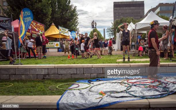 asheville, nc, usa. july 30, 2016.  leaf festival in downtown asheville with a man in front standing in hula hoops. in the background are tents with groups of people wandering through the venue. summer season. - asheville stock pictures, royalty-free photos & images