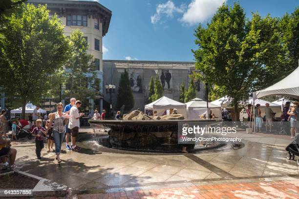 Asheville, North Carolina, USA. July 30, 2016. A child plays in a fountain while the parents look on. Other people walk around a festival in downtown Asheville during summer season.