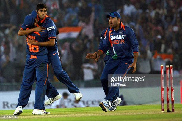 Ashish Nehra celebrates with Suresh Raina and Yuvraj Singh after dismissing Australia's Cameron White during the 4th one day international cricket...