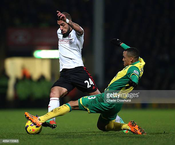 Ashkan Dejagah looks to get past Fulham's Martin Olsson during the Barclays Premier League match between Norwich City and Fulham at Carrow Road on...