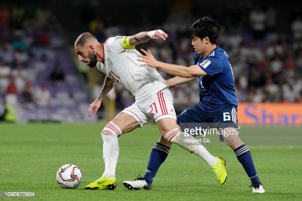 Ashkan Dejagah of Iran holds off Wataru Endo of Japan during the AFC Asian Cup semi final match between Iran and Japan at Hazza Bin Zayed Stadium on...