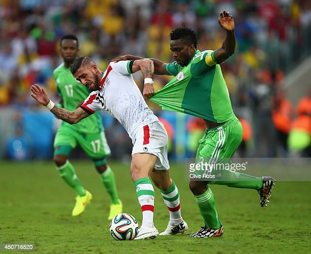Ashkan Dejagah of Iran pulls the jersey of Joseph Yobo of Nigeria during the 2014 FIFA World Cup Brazil Group F match between Iran and Nigeria at...
