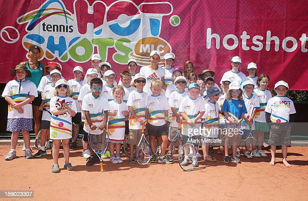 Ashleigh Barty of Australia and Chanelle Scheepers of South Africa pose with children for Kids For Tennis day during day three of the Hobart...