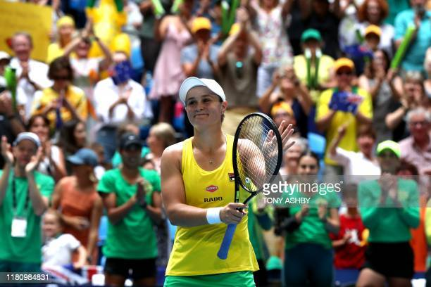 TOPSHOT Ashleigh Barty of Australia celebrates after winning the match against Caroline Garcia of France on day one of the Fed Cup Final tennis...