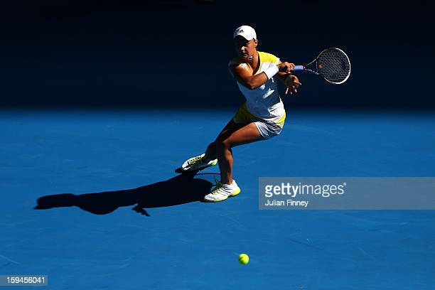 Ashleigh Barty of Australia plays a forehand in her first round match against Dominika Cibulkova of Slovakia during day one of the 2013 Australian...