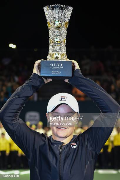 Ashleigh Barty of Australia poses with her trophy after beating Japan's Nao Hibino in their women's singles finals match of the WTA Malaysian Open...
