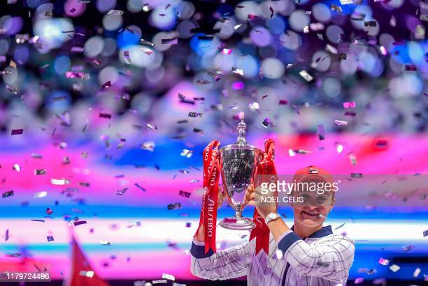 Ashleigh Barty of Australia raises her trophy after winning against Elina Svitolina of Ukraine in their women's singles in the WTA Finals tennis...