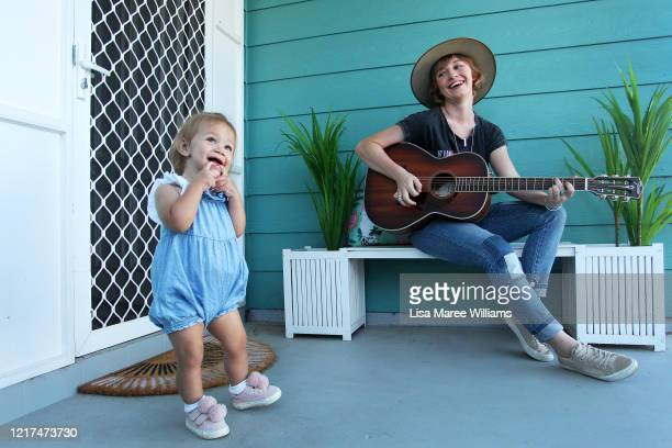 Ashleigh Dallas a Golden Guitar Winning musician plays guitar on her front porch whilst isolating at home with young daughter Harriet on April 06...