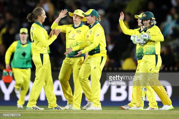 Ashleigh Gardner and Beth Mooney of Australia celebrate with their team after combining to dismiss Sophie Devine of New Zealand during game one of...