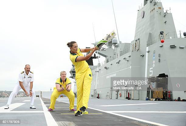Ashleigh Gardner bats as Sarah Beard keeps wicket and HMAS Canberra's Engineering Officer Commander Guy Lewis fields in the slips aboard the HMAS...