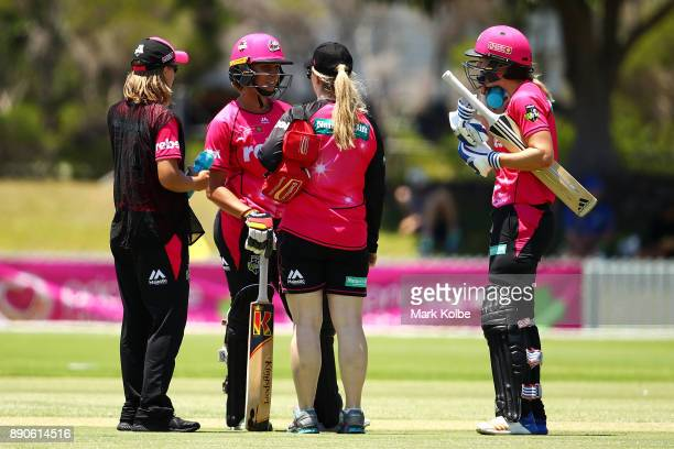 Ashleigh Gardner of the Sixers receives attention from the trainer after she was struck on the helmet while batting during the Women's Big Bash...