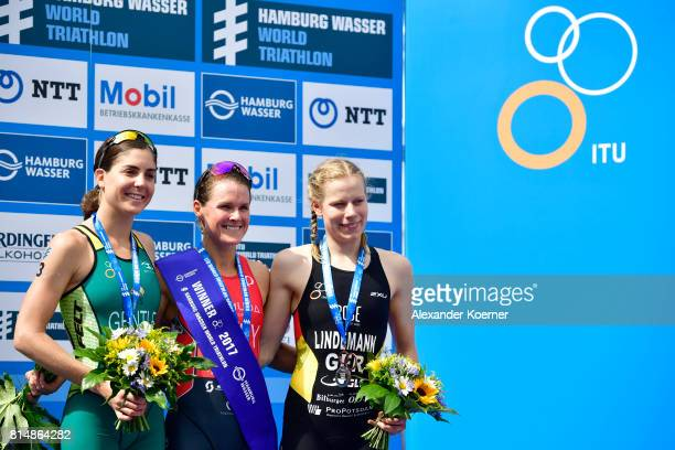 Ashleigh Gentle of Australia Flora Duffy of Bermuda and Lena Lindemann of Germany celebrate the sprint distance on stage at the Hamburg Wasser ITU...