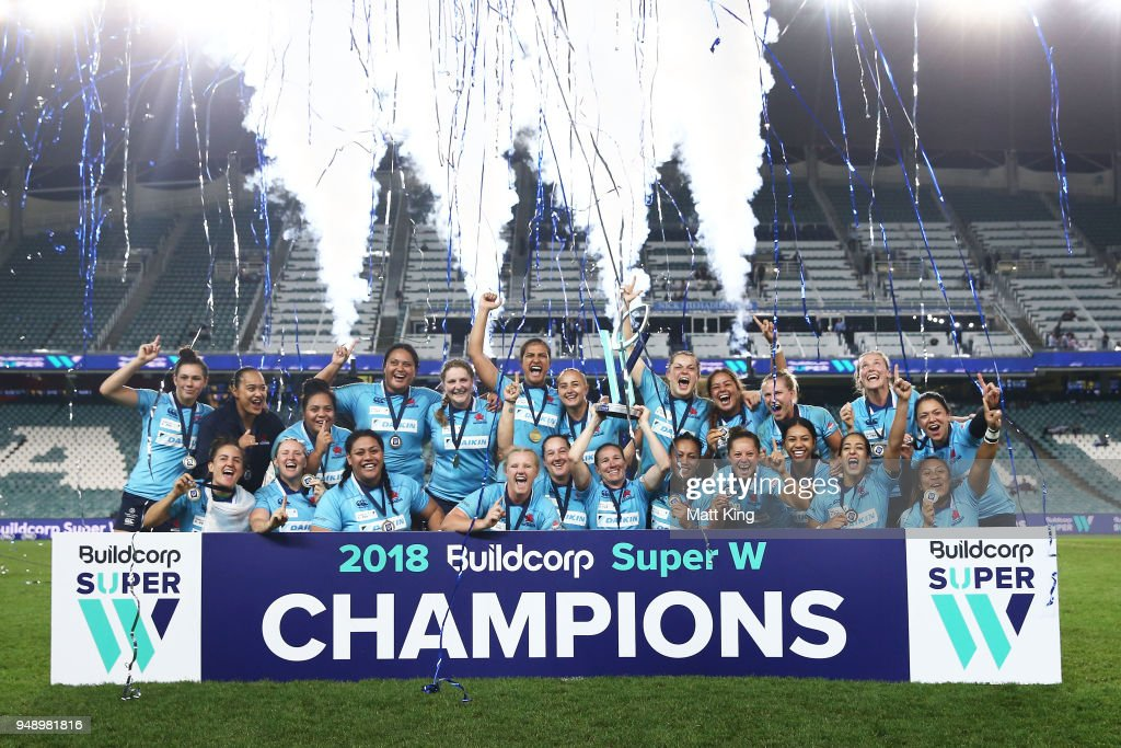 Ashleigh Hewson of New South Wales holds aloft the Super W trophy and team mates celebrate victory during the Super W Grand Final match between the the New South Wales Women and the Queensland Women at Allianz Stadium on April 20, 2018 in Sydney, Australia.