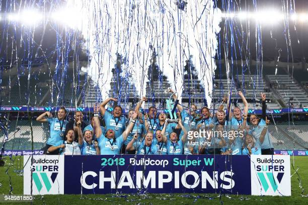 Ashleigh Hewson of New South Wales holds aloft the Super W trophy and team mates celebrate victory during the Super W Grand Final match between the...