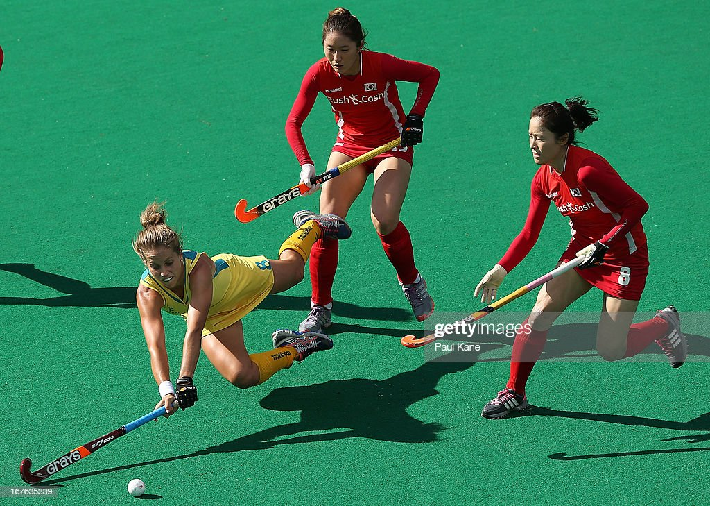 Ashleigh Nelson of Australia dives for the ball against An Hyo Ju and Kim Jong Hee of Korea during the International Test match between the Australian Hockeyroos and Korea at Perth Hockey Stadium on April 27, 2013 in Perth, Australia.