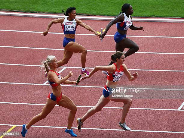 Ashleigh Nelson of Great Britain and Northern Ireland passes the baton to Anyika Onuora of Great Britain and Northern Ireland next to Christine...