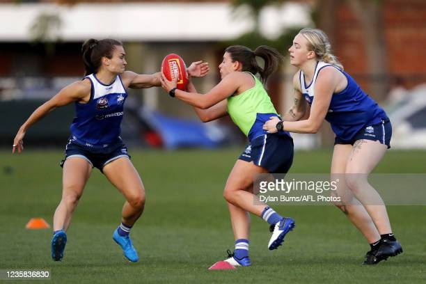 Ashleigh Riddell of the Kangaroos, Ellie Gavalas of the Kangaroos and Ella Maurer of the Kangaroos compete for the ball during the North Melbourne...