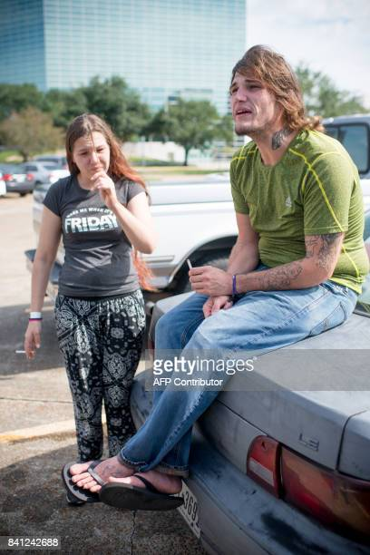 Ashley Atkeson and her partner Nathaniel Owens both of Orange Texas sit on their car outside the Lake Charles Civic Center in Lake Charles Louisiana...