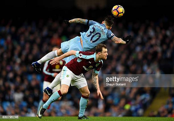 Ashley Barnes of Burnley and Nicolas Otamendi of Manchester City battle to win the ball in the air during the Premier League match between Manchester...