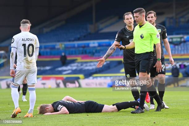 Ashley Barnes of Burnley argues with referee Robert Jones as Ben Mee is seen on the floor during the Premier League match between Leeds United and...