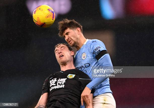 Ashley Barnes of Burnley competes for a header with John Stones of Manchester City during the Premier League match between Manchester City and...