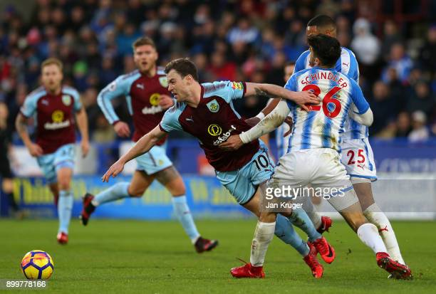 Ashley Barnes of Burnley is challenged by Christopher Schindler of Huddersfield Town during the Premier League match between Huddersfield Town and...